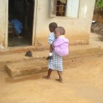 Aug 2010: An elder sister carrying her sibling to school
